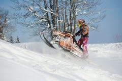 Athlète sur un motoneige se déplaçant les montagnes Photographie stock libre de droits