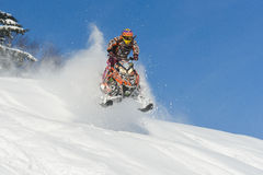 Athlète sur un motoneige se déplaçant les montagnes Image stock