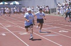 Athlètes de Jeux Olympiques spéciaux courant la course, UCLA, CA Image libre de droits