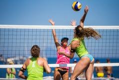 Athlètes féminins dans l'action pendant un tournoi dans le volleyball de plage Photographie stock libre de droits