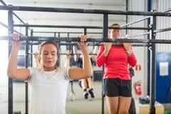 Athlètes faisant Chin-UPS au gymnase Photos stock