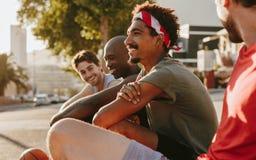 Athlètes s'asseyant sur le trottoir et parler Photos stock