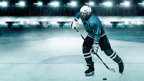 Athl?te de joueur de hockey de glace dans le casque et gants sur le stade avec le b?ton Tir d'action Concept de sport image stock