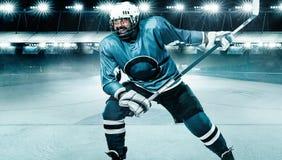 Athl?te de joueur de hockey de glace dans le casque et gants sur le stade avec le b?ton Tir d'action Concept de sport photos stock