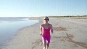 Athl?te ind?pendant de jeune femme courant sur la plage exer?ant le coureur f?minin sprintant la formation ? l'arri?re-plan ensol clips vidéos