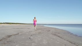 Athl?te ind?pendant de jeune femme courant sur la plage exer?ant le coureur f?minin sprintant la formation ? l'arri?re-plan ensol banque de vidéos