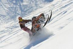 Athlet auf einem Schneemobil fahrung, das in die Berge sich bewegt Stockfoto