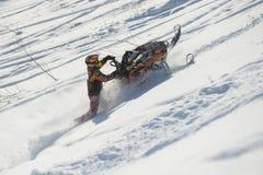 Athlet auf einem Schneemobil fahrung, das in die Berge sich bewegt Stockfotografie
