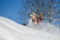 Athlet auf einem Schneemobil fahrung, das in die Berge sich bewegt Stockfotos