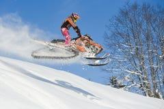 Athlet auf einem Schneemobil fahrung, das in die Berge sich bewegt Lizenzfreies Stockfoto