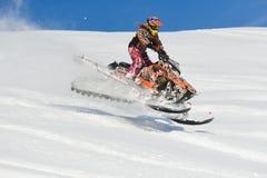 Athlet auf einem Schneemobil fahrung, das in die Berge sich bewegt Lizenzfreie Stockfotos
