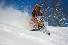 Athlet auf einem Schneemobil fahrung, das in die Berge sich bewegt Lizenzfreies Stockbild