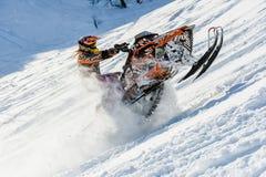 Athlet auf einem Schneemobil fahrung, das in die Berge sich bewegt Stockbilder