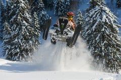 Athlet auf einem Schneemobil fahrung, das in die Berge sich bewegt Lizenzfreie Stockbilder