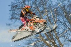 Athlet auf einem Schneemobil fahrung, das in die Berge sich bewegt Stockbild