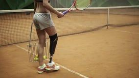 Athlet, behinderte Frau sammelt Tennisbälle im Korb, der mit einem Schläger sich hilft Abschluss oben stock video footage