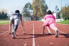 Athlet Couple Ready, zum des Staffellaufs zu beginnen stockfotografie