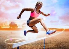 Athlet, der über Hürde auf dem Gebiet gegen helles Sonnenlicht läuft lizenzfreie stockfotografie