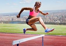 Athlet, der über Hürde im Stadion läuft stockfotografie