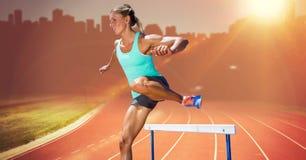 Athlet, der über Hürde läuft stockfotos