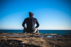 Athlet, der die Pause sitzt auf Felsen mit Seehorizont macht Stockbilder