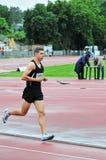Athlet, der in ein Rennen auf der Laufbahn läuft stockfotos