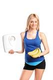 Athlet, der eine Gewichtskala und -bananen anhält lizenzfreies stockbild