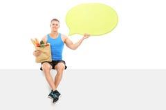 Athlet, der eine Spracheblase und -Einkaufstüte hält Stockfotografie