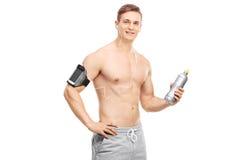 Athlet, der eine Wasserflasche hält und Musik hört Stockfotografie
