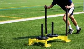 Athlet, der einen Schlitten mit Gewichten auf einem Rasenfeld drückt stockfoto