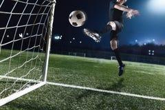 Athlet, der Fußball in ein Ziel nachts tritt lizenzfreies stockbild