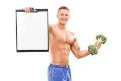 Athlet, der Klemmbrett und einen Brokkolidummkopf hält Stockfoto