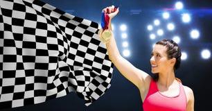 Athlet, der Medaillen gegen Zielflagge im Stadion hält Stockbild