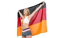 Athlet, der mit deutscher Flagge nach Sieg aufwirft Stockfotografie