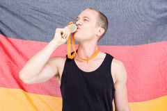 Athlet, der mit Goldmedaille vor deutscher Flagge aufwirft Stockfotos