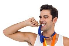 Athlet, der mit Goldmedaillen um seinen Hals aufwirft Stockfotografie