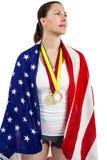 Athlet, der mit Medaillen der amerikanischen Flagge und des Goldes um seinen Hals aufwirft Stockbild