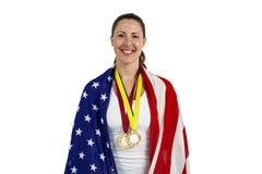Athlet, der mit Medaillen der amerikanischen Flagge und des Goldes um seinen Hals aufwirft Lizenzfreies Stockfoto