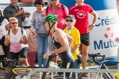 Athlet, der mit seinem Fahrrad zum Fahrradkurs läuft Lizenzfreie Stockfotos