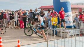 Athlet, der mit seinem Fahrrad zum Fahrradkurs läuft Stockfotografie