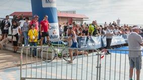 Athlet, der mit seinem Fahrrad zum Fahrradkurs läuft Lizenzfreie Stockfotografie