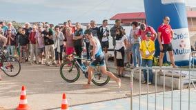 Athlet, der mit seinem Fahrrad zum Fahrradkurs läuft Stockfoto