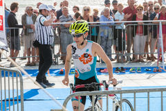 Athlet, der mit seinem Fahrrad zum Fahrradkurs läuft Stockbild