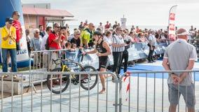 Athlet, der mit seinem Fahrrad zum Fahrradkurs läuft Stockbilder
