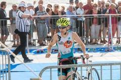 Athlet, der mit seinem Fahrrad zum Fahrradkurs läuft Lizenzfreies Stockbild