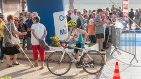 Athlet, der mit seinem Fahrrad zum Fahrradkurs läuft Lizenzfreies Stockfoto