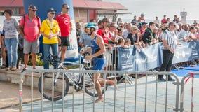 Athlet, der mit seinem Fahrrad zum Fahrradkurs läuft Lizenzfreie Stockbilder