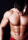 Athlet, der seine Abdominal- Muskeln zeigt Stockbilder