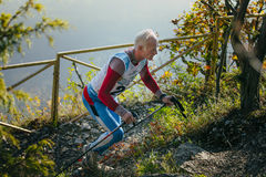 Athlet des alten Mannes, der auf Gebirgspfad mit nordischen Wanderstöcken läuft Stockfoto