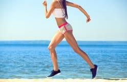 Athlet des jungen Mädchens, kurz gesagt und Spitze laufend auf dem Strand im Sommer, Morgenübung Lizenzfreie Stockfotos